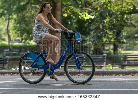 New York, September 17, 2016: A young woman is riding a citibike in Central Park.