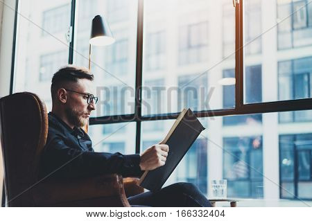 Intelligent stylish businessman reading black book while sitting in vintage chair at his modern office.Young man relaxing after work day.Panoramic windows on blurred background.Horizontal, film effect