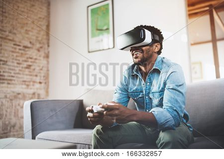 Concept of technology, gaming, entertainment and people.Happy african man enjoying virtual reality glasses while relaxing on sofa.Smiling young guy with VR headset playing video game at home.Blurred