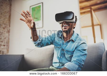 Concept of technology, gaming, entertainment and people.Happy bearded african man enjoying virtual reality glasses while relaxing on sofa at home.Blurred background