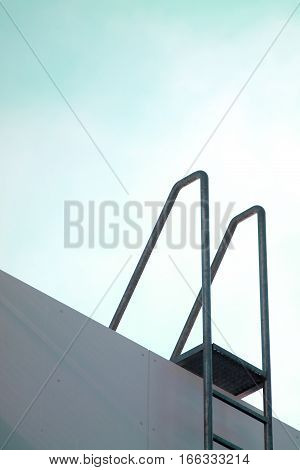 Roof access ladder with metal handholders against cyan blue sky.