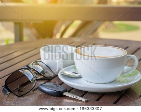 Hot Coffee Latte In A Glass Of White Paste On A Wooden Table, With Sunglasses And Car Keys. Travel C