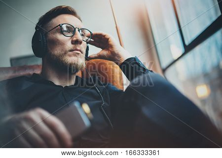 Portrait handsome bearded man wearing glasses, headphones listening to music at modern home.Guy sitting in vintage chair, holding smartphone and relaxing.Panoramic windows background.Blurred background