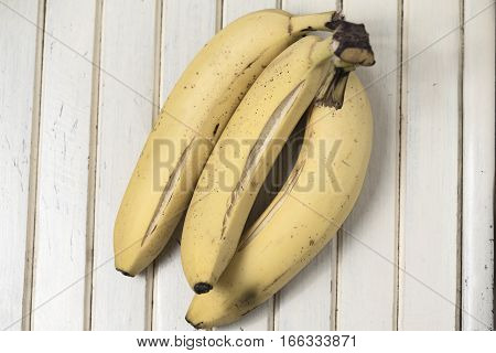 Ripe three bananas on a vintage surface