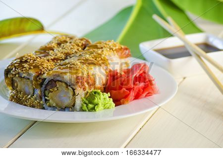 sushi with eel and shrimp tempuro on a plate and a white background
