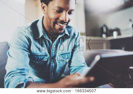 Smiling bearded African businessman using tablet while sitting on sofa at his modern home.Concept of young people working mobile devices.Closeup with a selected focus.Blurred background