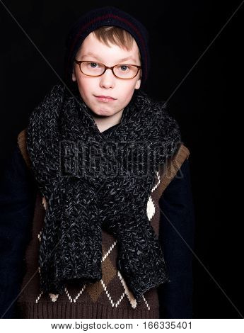 small smiling boy or cute nerd kid in glasses hat and fashionable knitted scarf on black background
