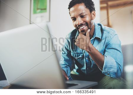 Smiling young African man making video call with friends while sitting on sofa at his modern office.Concept of happy business people.Blurred background, flare effect