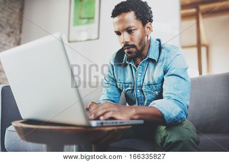 Concentrated bearded African man working at home while sitting on the sofa.Concept of young people using mobile devices.Blurred background