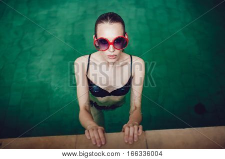 Sexy brunette woman in funny sunglasses with a beautiful professional make up floating in the pool.