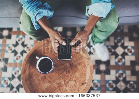 Top view of african man using smartphone while sitting on sofa at home.Concept people working with mobile gadget.Black coffee on the wooden table.Blurred background