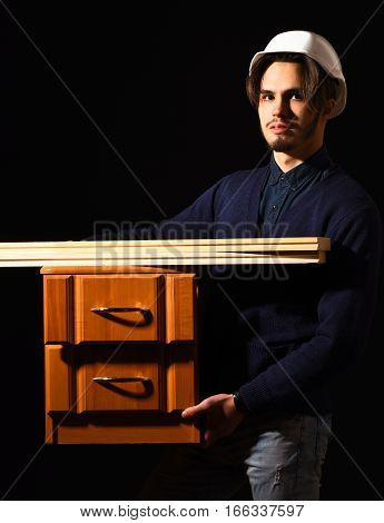handsome bearded builder or foreman in blue sweater and helmet on serious face holding wooden bedside with boards on black studio background