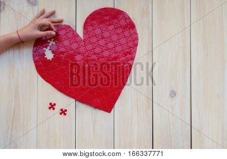 Red heart shaped puzzle on white wooden background. Concept for Love or St Valentines day.Copy space