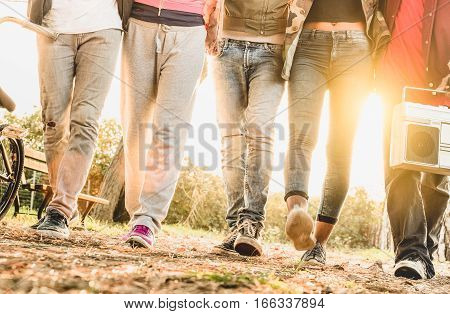 Legs view of friends walking in city bike park with backlight and sunflare halo - Friendship concept with multiracial young people having fun together - Soft blurred motion with shallow depth of field