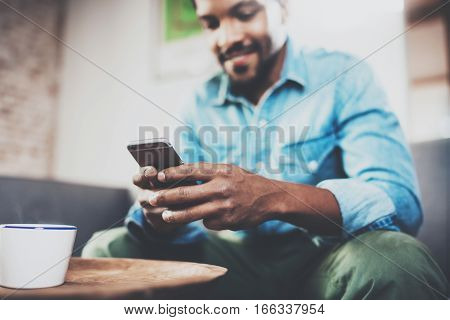 Young happy African man using smartphone while sitting on sofa at home.Concept people working with mobile gadget.Selective focus hand.Blurred background