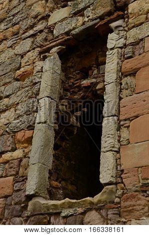 An external view of a window frame on a ruined building near Elie