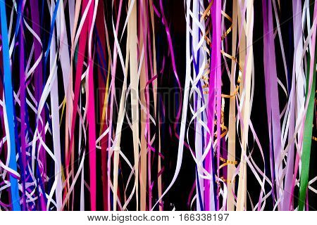 A collection of curling colored ribbons against a black background.