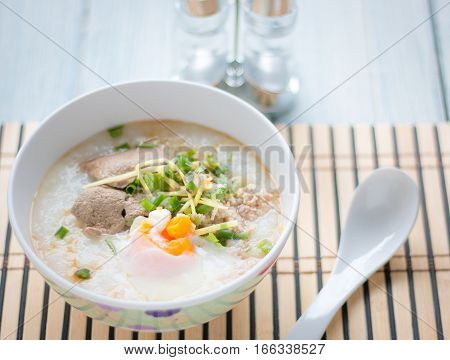 Traditional Chinese Porridge Rice Gruel In Bowl On White Wooden Background.