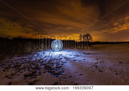 Luminous sphere on a frozen lake and the light of the full moon
