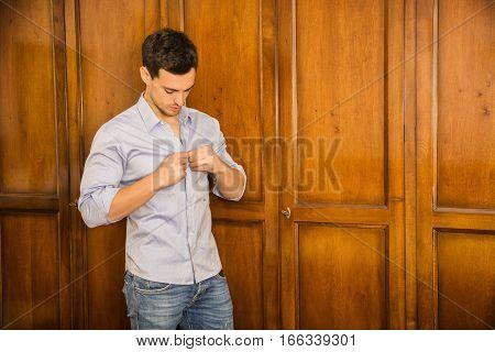 Sexy handsome young man standing wearing shirt in his bedroom against wooden wardrobe door