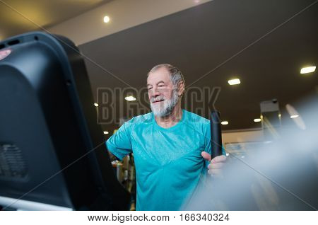 Fit senior man in sports clothing in gym doing cardio workout, exercising on elliptical trainer machine. Sport fitness and healthy lifestyle concept.