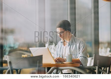 Handsome businessman in casual wear and eyeglasses is using a laptop. Productive morning. Busy young freelancer working in cafe with his laptop. He is trying to find some new ideas for his business