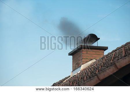 Chimney with a black smoke coming out.