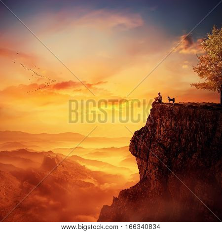 Young man with his faithful dog standing together on the peak of a cliff watching the sunset over valley. Recalling childhood memories friendship between human and animal.