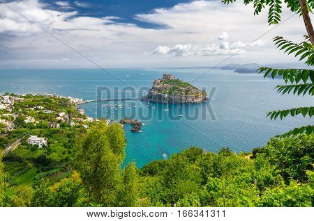 Aerial view on Aragonese castle through green oliage, Ischia, Italy