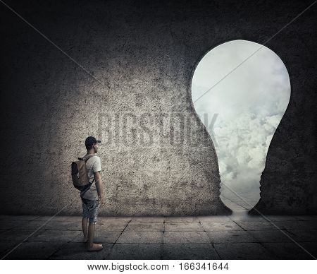 Conceptual image with a person standing in a dark room in front of a bulb shaped doorway. Escape opportunity entrance to another world.