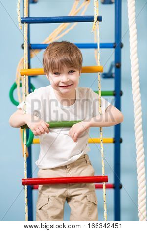 Little child boy playing sports at sport center. Kid boy standing on a rope ladder.