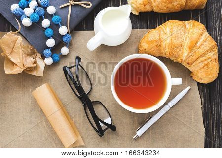 French Croissant, Glasses, Tea And Notebook. Workplace Concept