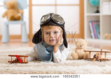 close-up portrait of a child boy playing with a wooden airplane and dreaming be aviator