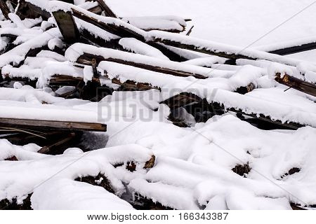 Pile of wooden rubble covered in snow.