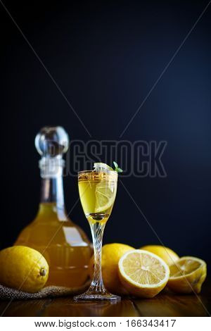 sweet lemon alcoholic brandy in the decanter on a dark table