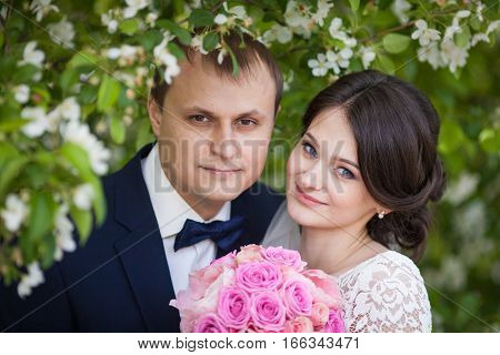 Portrait of young newlywed groom and bride with pink wedding bouquet in blooming garden
