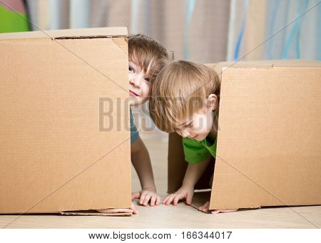 Child and toddler brothers playing in cardboard boxes