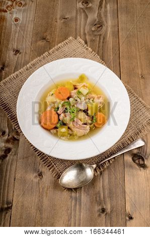 pork stew with carrot celery potato and parsley and plate on jute
