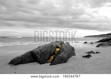 Split boulder on beach with smaller rocks filling up the crack, black and white with crack coloured.
