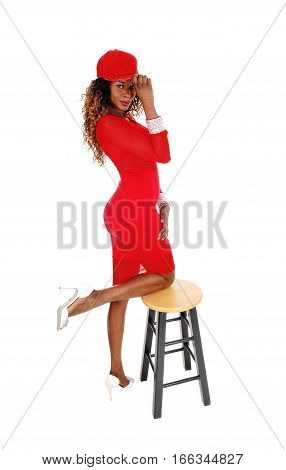 A lovely young African American woman in a tight red dress and red cap kneeling with one leg on chair isolated for white background.