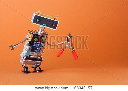 Service and repairment concept. Abstract robotic toy worker with red pliers. Fun kindly handyman character, colorful head red blue light bulbs eyes. orange background copyspace