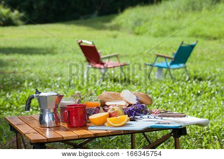 picnic, view of picnic table with various fruits, juice, pancake, coffee and vegetable at the camping area.