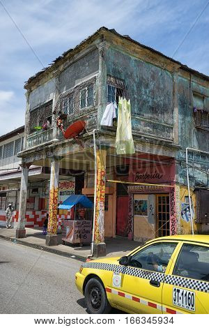 June 9 2016 Colon Panama: a yellow taxi drives by an unkept building in the port town