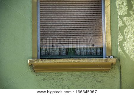 Photo of a window with green colour, blind and sunlight