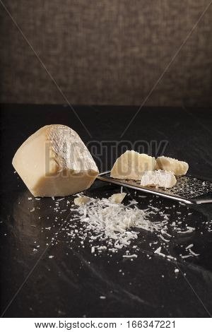Large grated parmesan cheese with a grater