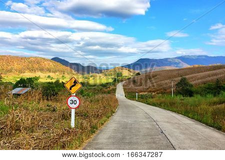 Concrete road with traffic sign and natural view at Pai, Thailand.