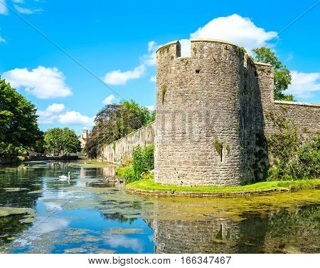 Moat and boundary wall of Bishop's Palace in Wells Somerset. Some swans on water surface. Copy space in sky.