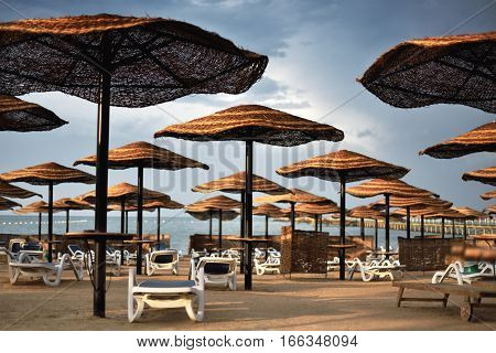 Moody Image Hotel Beach Area With Umbrellas And Sun Loungers Cloudy Weather, Horizontal