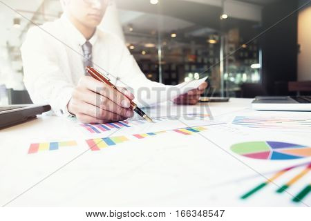 Startup businessman working with business documents on office table with graph financial diagram. Business idea concept.