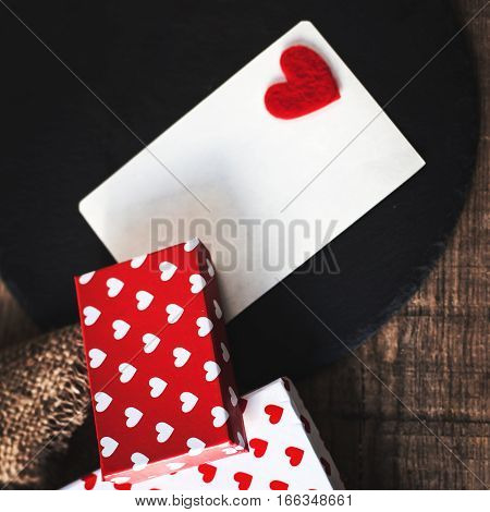 Holiday background with gift boxes with hearts card for messaage and red hearts. Valentines day